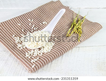 Rice grain in white spoon on a napkin at wood background - stock photo