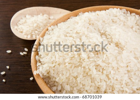 rice grain in wooden spoon and plate - stock photo
