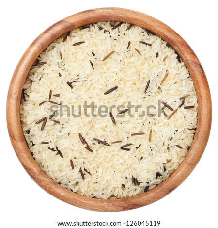Rice grain uncooked in wooden  bowl, isolated on white