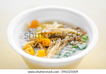 rice gruel in bowl on yellow table - stock photo