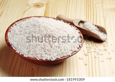 Rice in a bowl and scoop on wooden table