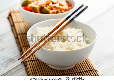 rice in a chinese dishware with sweet and sour veggies in the background. - stock photo