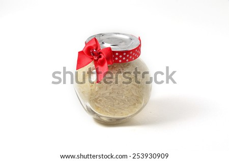 Rice in a glass container. Shoot over white background. Shallow depth of field. Focus on the important part. - stock photo