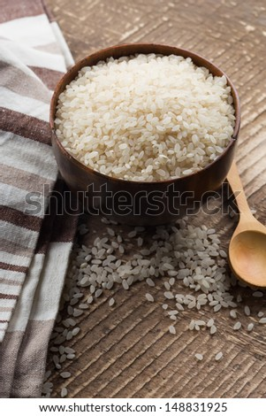 Rice in bowl on wooden background. Selective focus.