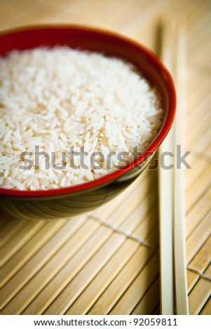 rice in bowl with chopsticks on wooden structured background - stock photo