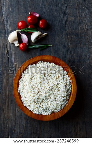 Rice in bowl with raw vegetable for cooking  on vintage wood texture, top view - stock photo