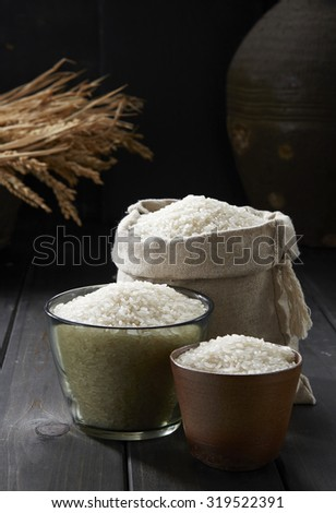 Rice in glass cup and a bag on wooden background