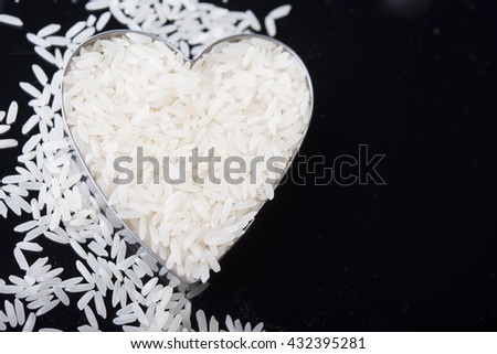 Rice in heart bowl on white rice background - stock photo