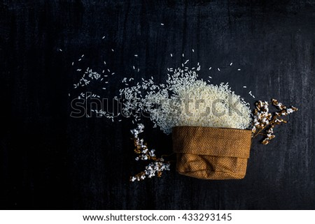 rice in sack,white rice in burlap sack with rice grain on the black wood