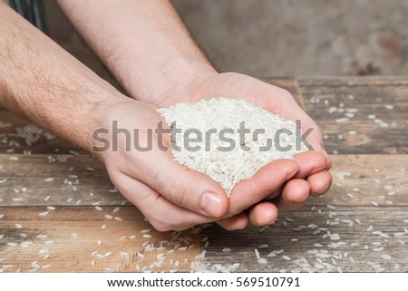 Rice in the hands on the wooden table in the kitchen. Healthy eating and lifestyle.