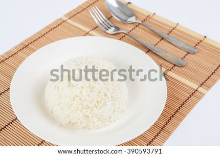 Rice in white dish on mat made of wood.And Spoon the side put on the white background.