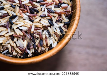 Rice in wood bowl - stock photo