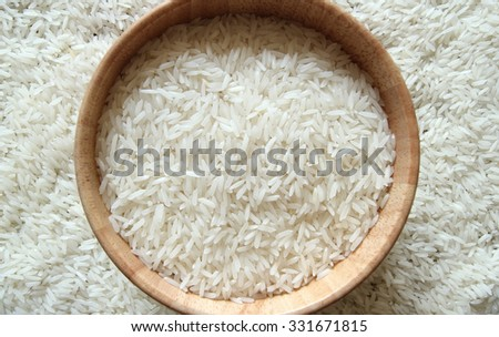 Rice in wooden bowl on white rice background - stock photo