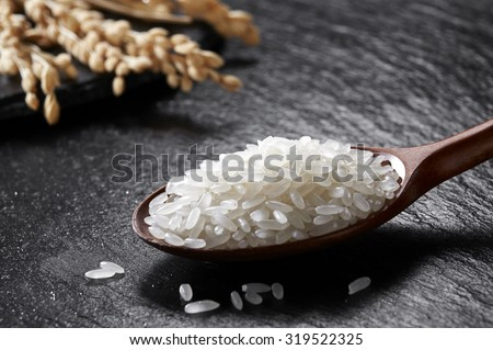 Rice in wooden Spoon on black stone background  - stock photo