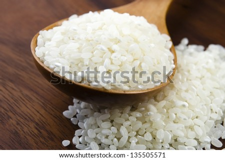 Rice in wooden spoon on kitchen table