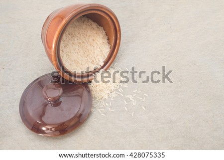 Rice inside a ceramic plate with spillover,wooden background