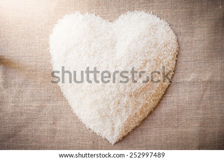 Rice laid out in a heart shape on the sackcloth. The view from the top - stock photo