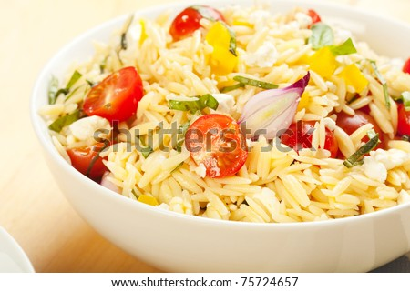 Rice like pasta orzo in a salad with basil, tomato, feta, and onion