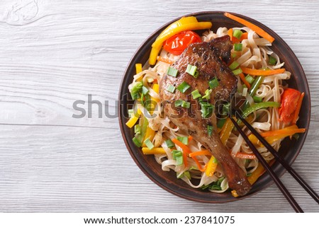 Rice noodles with duck leg and vegetables on a plate. top view of a horizontal  - stock photo