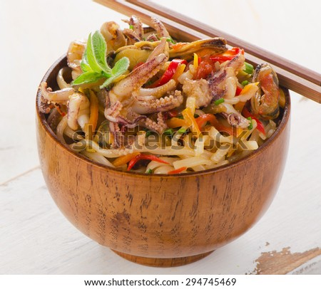 Rice noodles with seafood closeup in a bowl. Selective focus