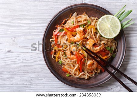Rice noodles with shrimps and vegetables close-up on the table. top view of a horizontal - stock photo