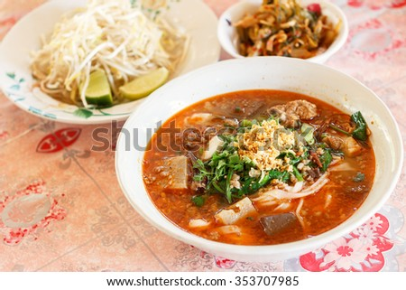 Rice noodles with spicy pork sauce (Nam ngiao) is a noodle soup or curry of the cuisine of the Tai Yai people. Nam ngiao has a characteristic spicy and tangy flavor. thai food. - stock photo