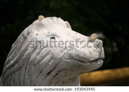 Rice offering on a statue at a Buddhist temple in Luang Prabang in northern Laos in South East Asia. - stock photo