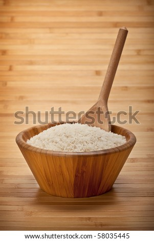 Rice on bowl and wooden spoon - stock photo