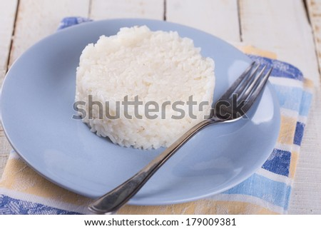 Rice on plate on wooden background. Selective focus. - stock photo