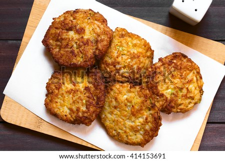 Rice patties or fritters made of cooked rice, carrot, onion, garlic and celery stalks, photographed overhead with natural light