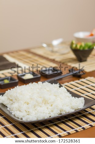 Rice plate in a plate ready to make japanese sushi rolls, with principal ingredients in the background. Selective focus in rice. - stock photo