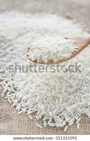 rice. rice grains in wooden spoon and rice grain background on jute cloth.