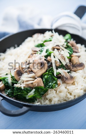 Rice (risotto) with mushrooms, parmesan and spinach close up on blue wooden background. Italian cuisine. - stock photo