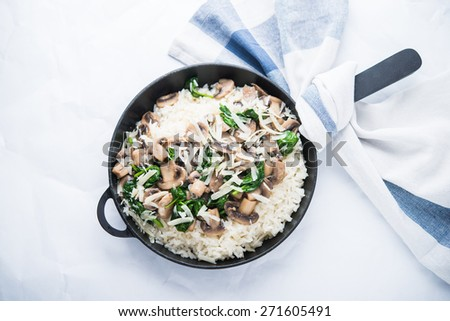 Rice (risotto) with mushrooms, parmesan and spinach top view on white background. Italian cuisine. - stock photo