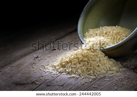 rice runs out of a ceramic bowl on weathered wood, copy space in the dark background - stock photo