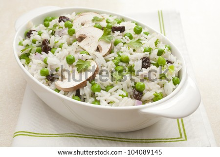 Rice salad with peas and mushrooms. Vinaigrette is added to hot cooked rice along with raisins, when cool peas, mushrooms, onion and parsley are added.
