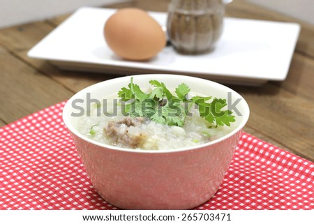 Rice Soup with pork and machines in a white Cup. With eggs and cooked as a visual component. - stock photo