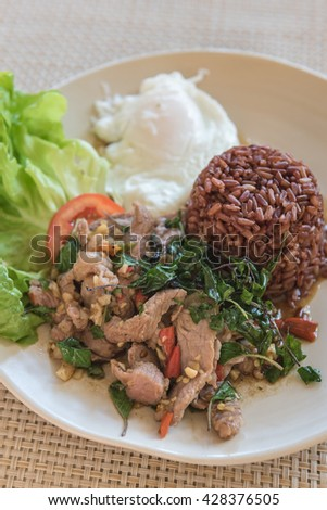 Rice topped with stir-fried beef and basil with  fried egg in restaurant