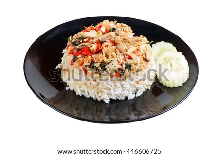 Rice topped with stir fried crab meat and basil in black dish on white background