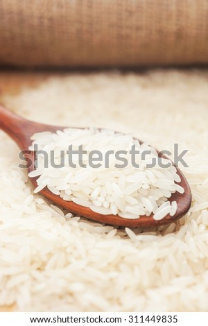 Rice, White rice in wooden spoon with hemp background, Selective focus