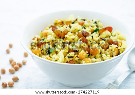 rice, wild rice, chickpeas with raisins and herbs on a white background. the toning. selective focus - stock photo
