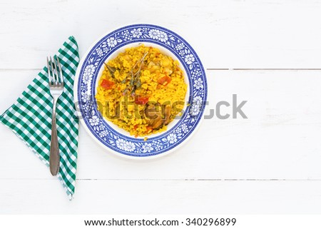 Rice with chicken and vegetables in bowl on wooden table - stock photo