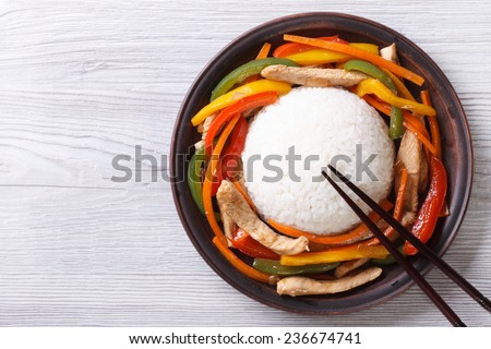 Rice with chicken, vegetables and chopsticks close-up on the table. top view of a horizontal  - stock photo