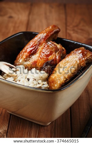 Rice with fried mushrooms and baked chicken wings on dark wooden background. Chinese cuisine. Selective focus