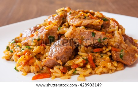Rice with meat and vegetables in a plate on wooden table - stock photo