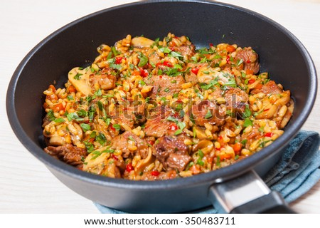 Rice with meat, vegetables and mushrooms in a frying pan - stock photo