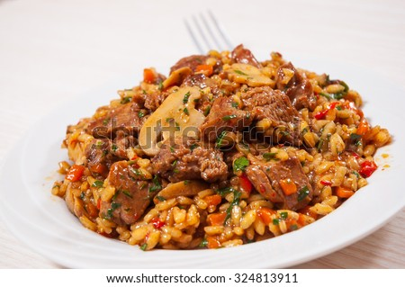 Rice with meat, vegetables and mushrooms on plate - stock photo