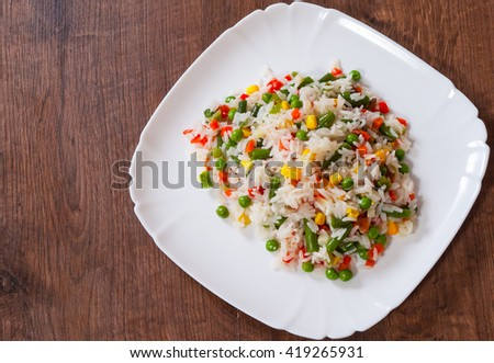 Rice with mixed vegetables on white plate - stock photo