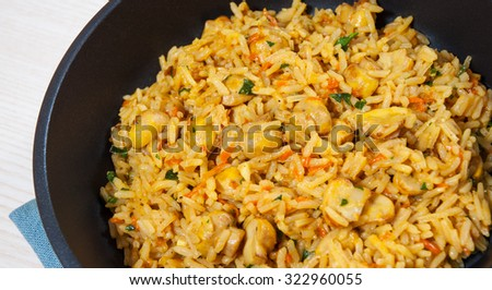 rice with mushrooms in a frying pan - stock photo