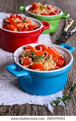 Rice with paprika and thyme in a ceramic dish - stock photo